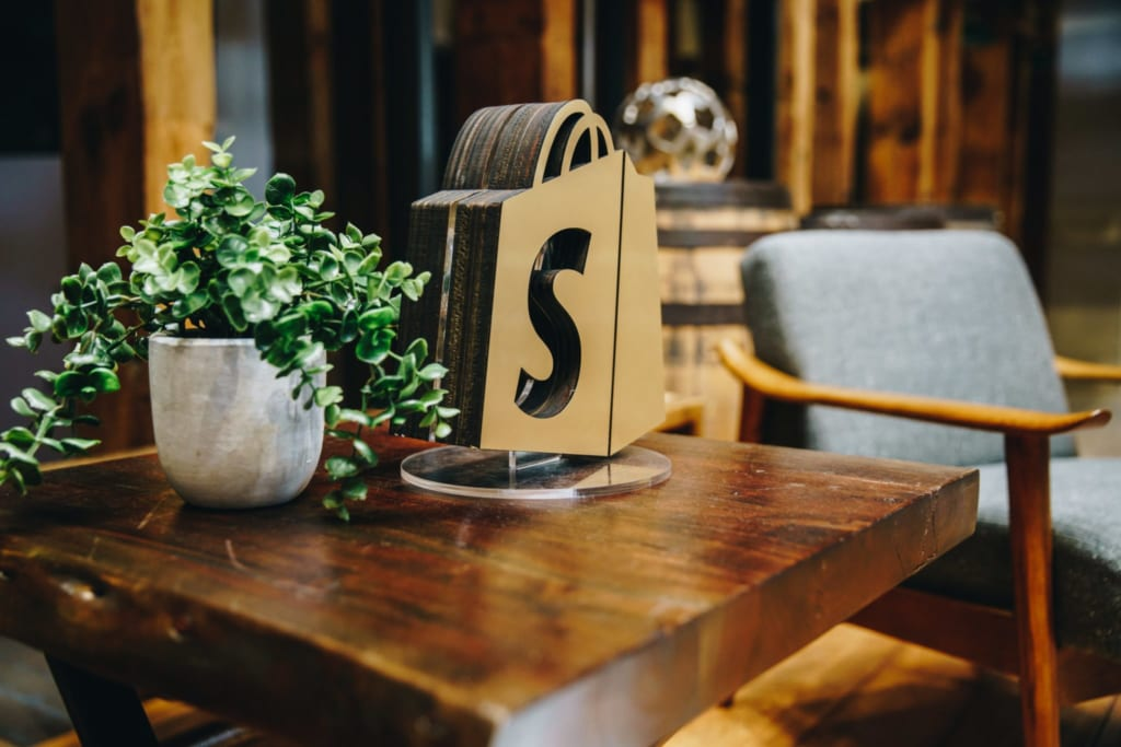 A cutout of the Shopify logo placed on a coffee table